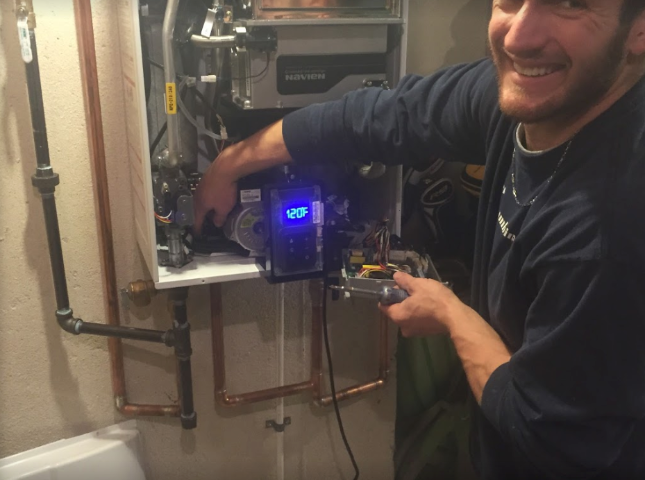 plumber from premier plumbing servicing a water heater