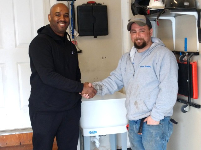 customer and plumber shaking hands after successful utility sink installation