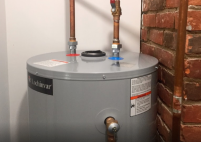 conventional water heater service with brass pipe near brick wall